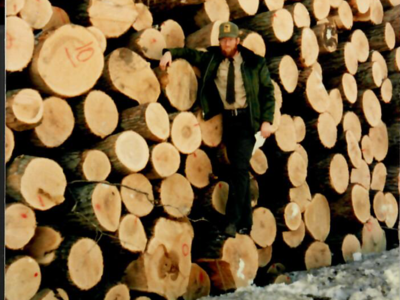 Figure 7.  Forester Jim Edgar with log pile from timber sale in the winter of 1985/86.  Note the exceptionally sound boles with very little rot.